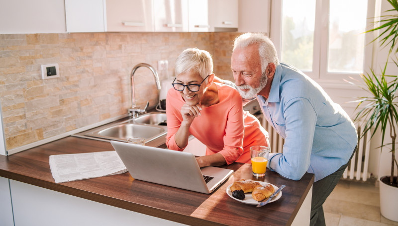 couple looking at laptop in kitchen over breakfast