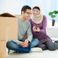 Muslim couple looking at mobile phone with packing cases Thumb