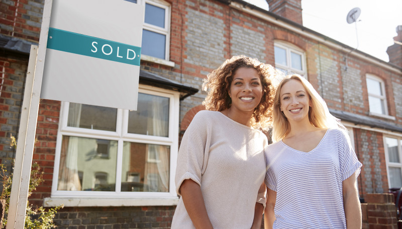 Two women next to sold sign