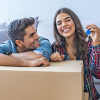 happy couple with packing box and door key thumb