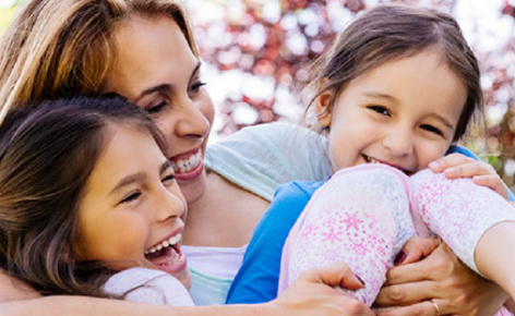 A mother and her two daughters smile