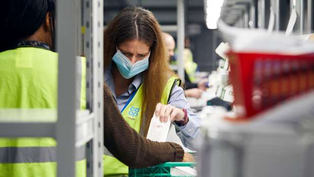 Image of Co-op Health colleague in PPE working dispensing medication.