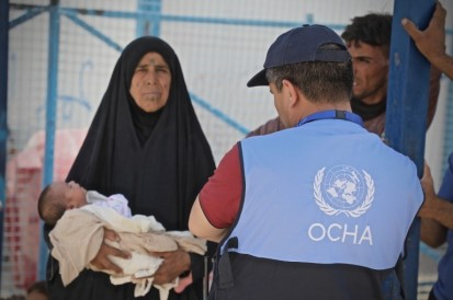 Woman holding child and OCHA officer
