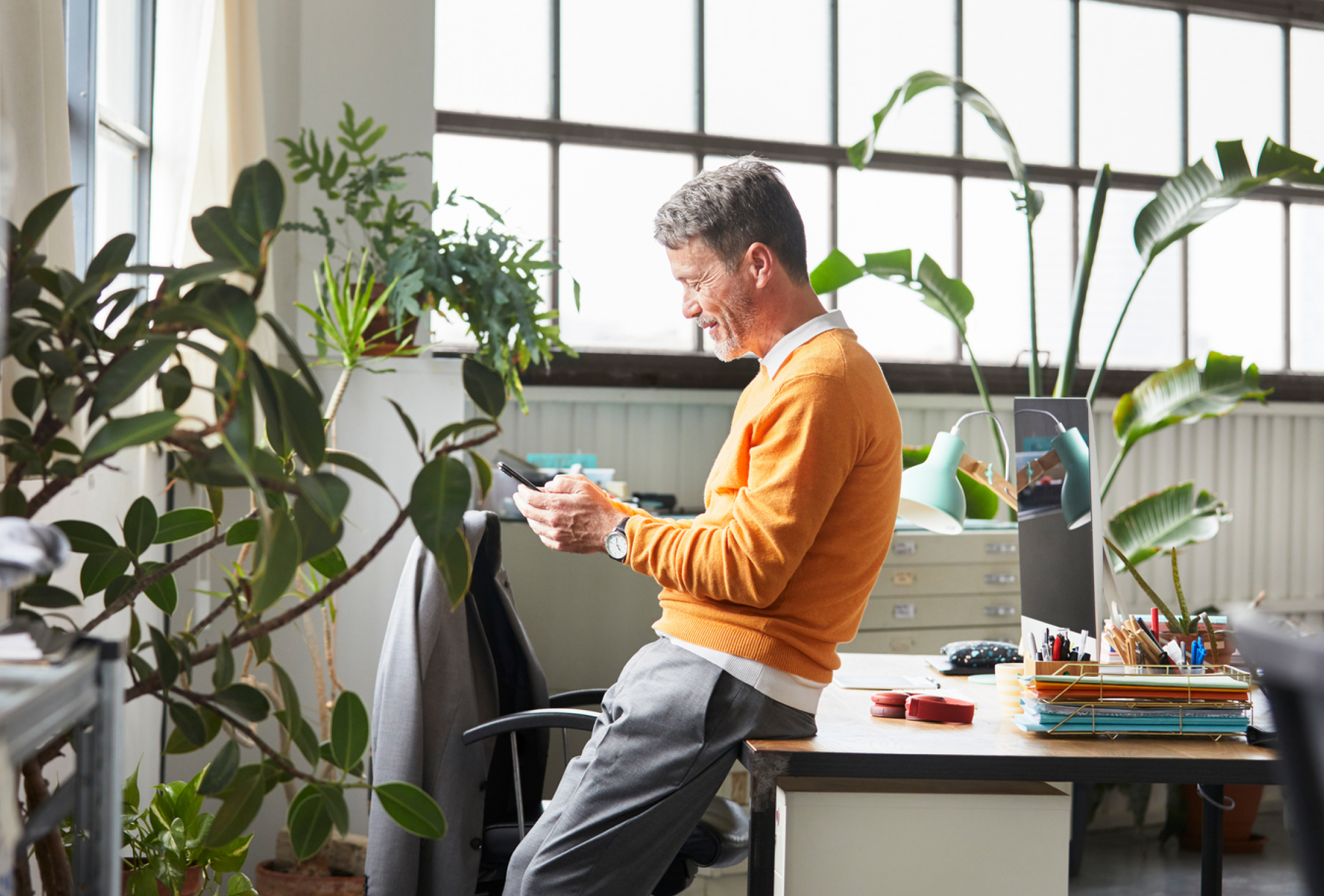 Photo of a man looking at his phone in a plant-filled office