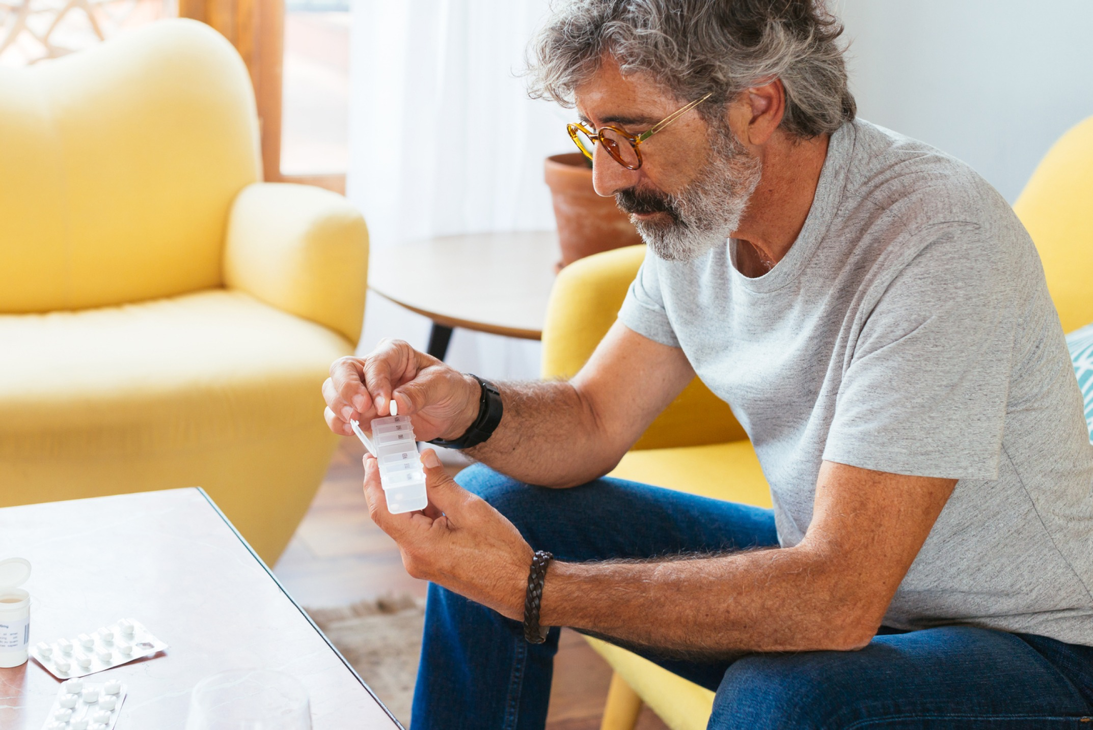 Older man sitting down with a pill container