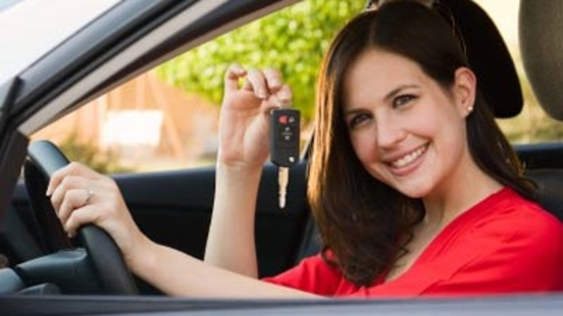 image of a lady holding a car key