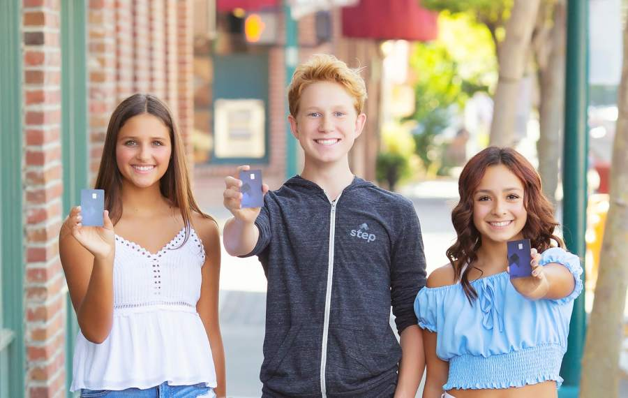 3 Teenagers holding up a Step Card smiling