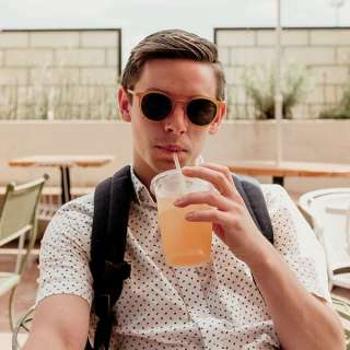 Guy drinking a fountain drink wearing dark sunglasses while looking cool
