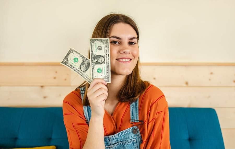 Teenage girl holding up money