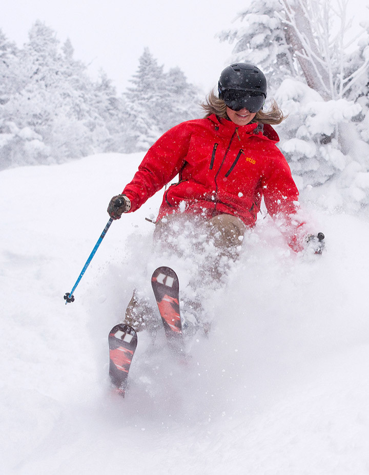 Skier smiling while spraying powder at Sugarbush, VT