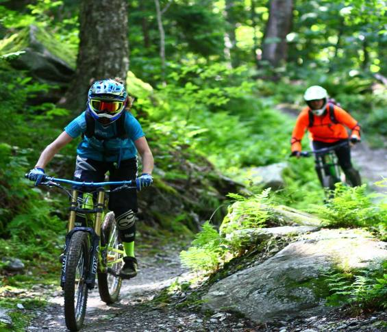 Mountain bikers cruising through trees at Sugarbush, VT