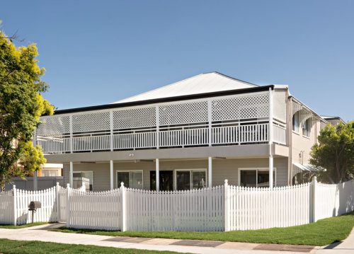 Picture of the property from the street, double story house with big windows, balcony and front yard and a white pickett fence