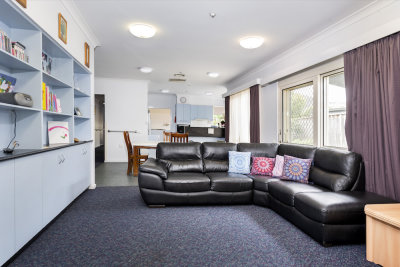 Interior image of a lounge room, light blue book case on the left and L-shaped black sofa on the right