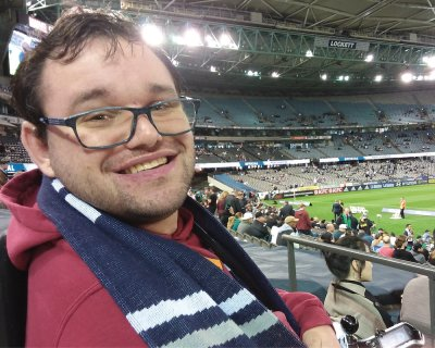 Picture of Jono watching a game at a sports stadium in a red jumper and blue scarf