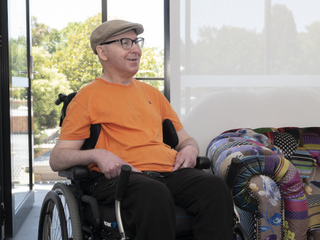 person in a manual chair wearing an orange t-shirt and a beret