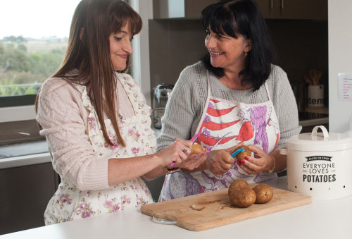 two people peeling potatoes wearing aprons in a kitchen