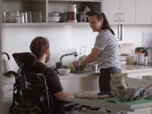 Person in a power chair in their kitchen with their support worker