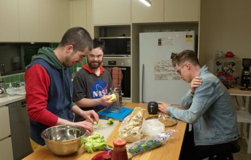 Three people in a kitchen preparing a meal