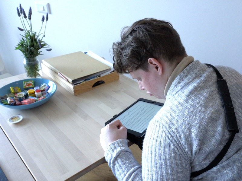 a person using a tablet device sitting at a table