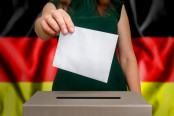 Woman putting her vote in a ballot box, German flag behind her