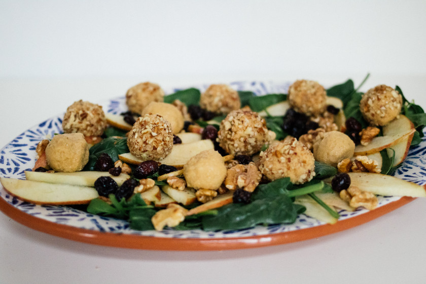 R129 vegan cheese balls on a salad with apple & cranberry