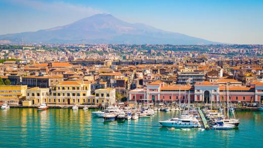 Europe - Italy - Sicily - Coast of Catania cruise port seen from the bat, blue skies and blue ocean and smoking volcano.
