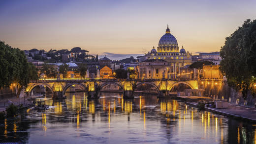 Europe, Italy, Rome, St Peters Basilica is seen from the Tiber River as the sunset casts the scene in purple and orange light.