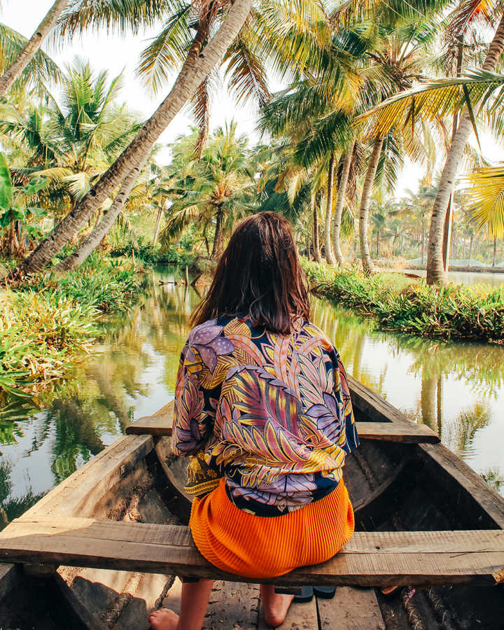 Woman on a wooden boat on a gorgeous tropical river