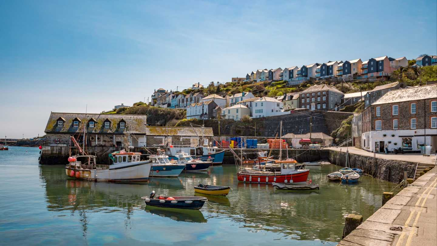 View of boats moored in a harbor in Cornwall, England