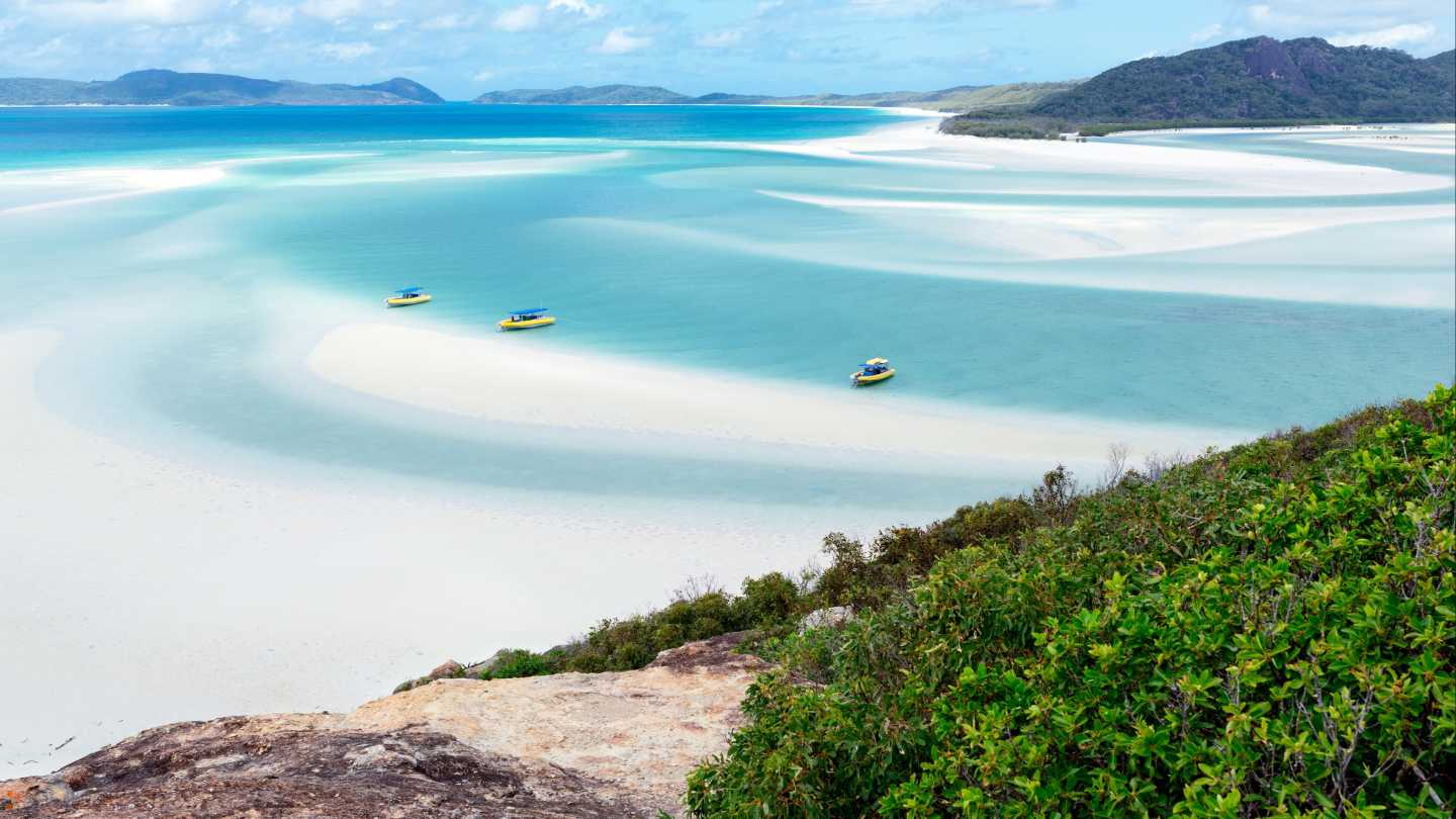 The blue waters of Whitehaven Beach on a sunny day.