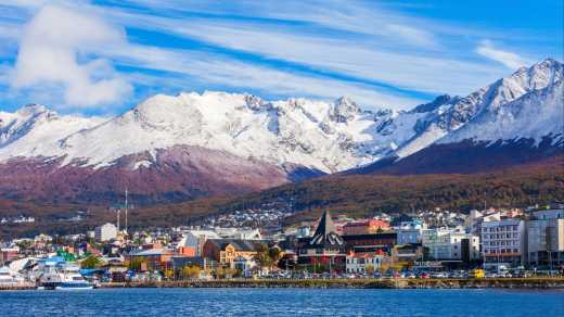 South America, Argentina, view of Ushuaia offshore with snowy mountains in the background.