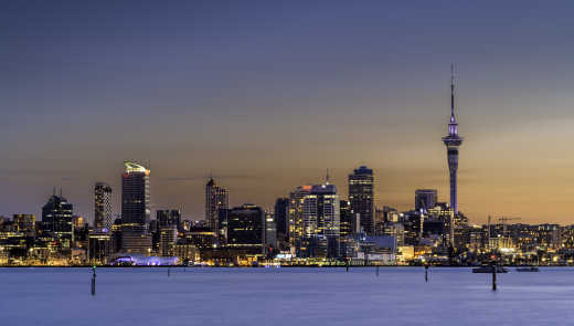Oceania, New Zealand, view of the Auckland skyline at sunset viewed from offshore.