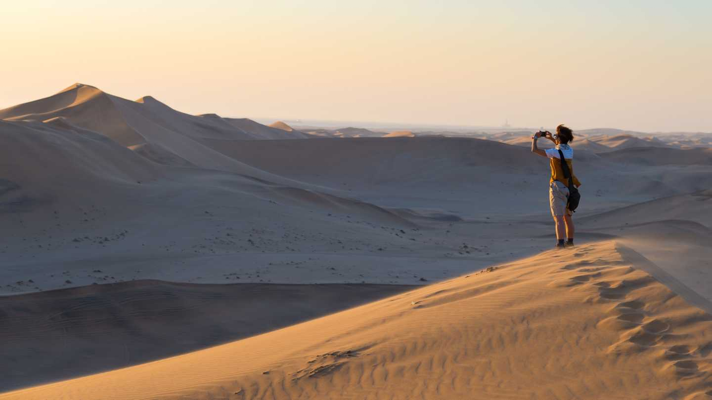 A women photographs the sand dunes in Namibia
