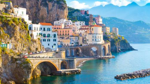 Europe, Italy, Amalfi Coast, colorful cliffside houses looking over a blue bay. Mountain silhouettes and blue sky in the background.