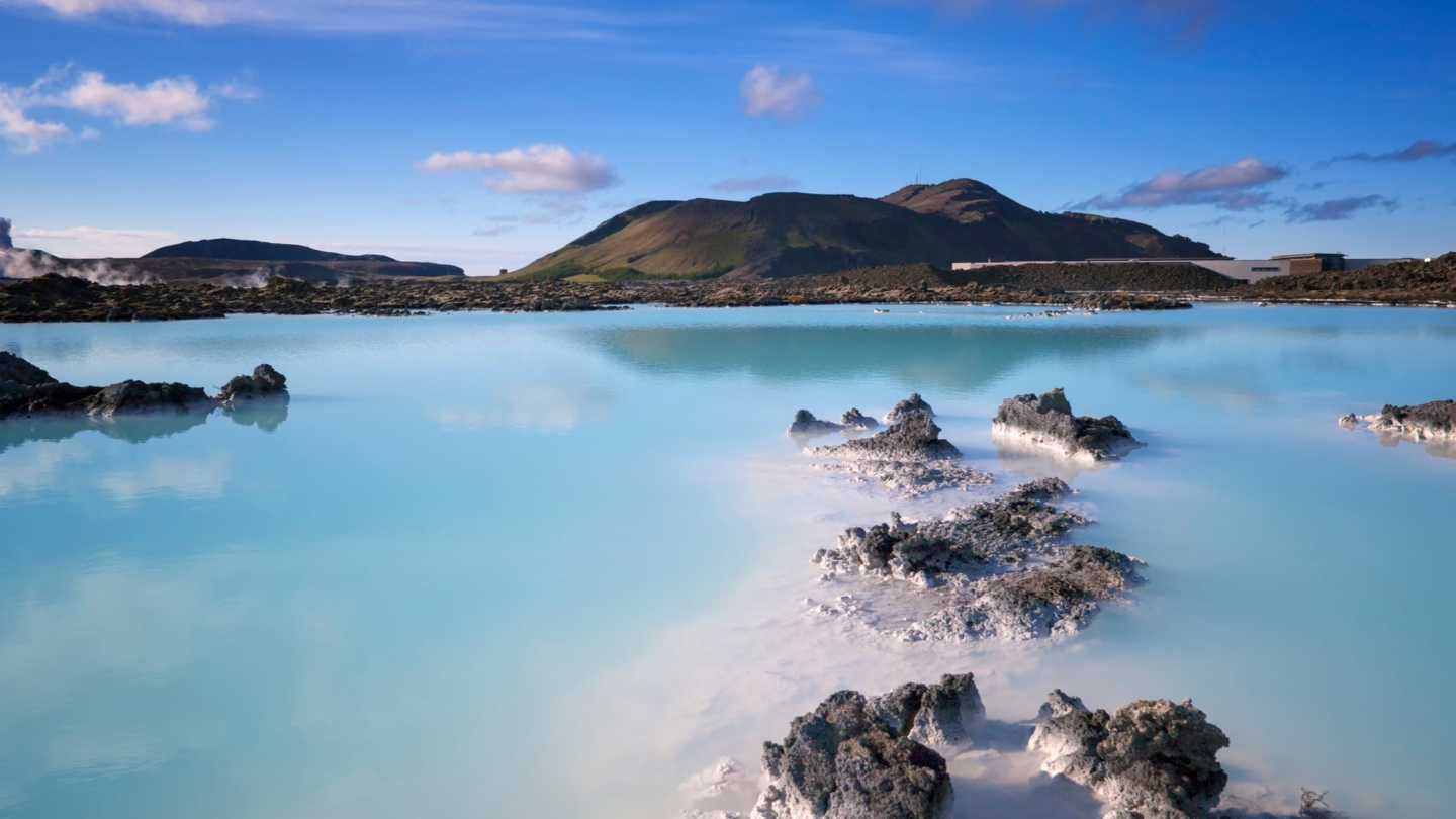 A large, blue natural spa in Iceland with mountains in the distance