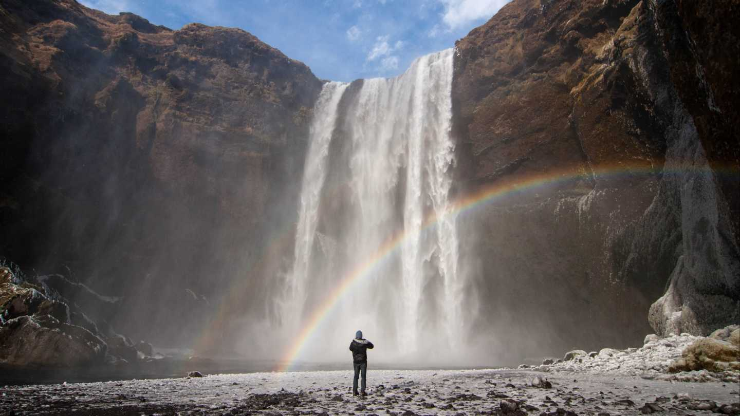 Europe, Iceland, Skógafoss Waterfall cascades from a cliff with a rainbow.