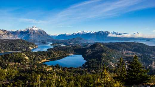 South America, Argentina, Bariloche, view from above of Nahuel Huapi Lake surrounded by forest and with snowy mountains in the background.