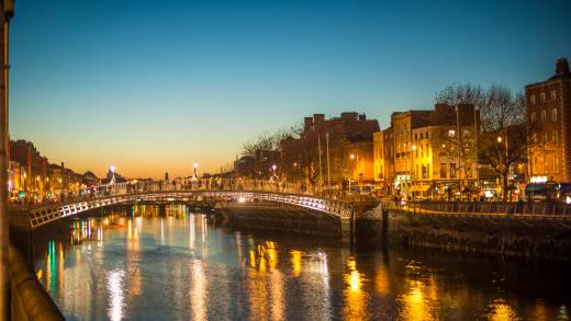 Europe, Ireland, Dublin, Ha'penny Bridge at dusk with the city lights reflected in the water below.