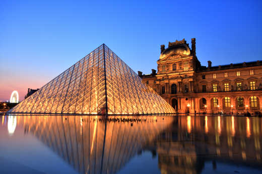 Discover amazing attractions like the Louvre, pictured here at night, as part of a Paris vacation package
