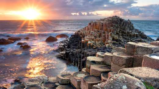 Discover the Giant's Causeway on a Game of Thrones Ireland tour. The sky is purple and the water breaks on the basalt columns.