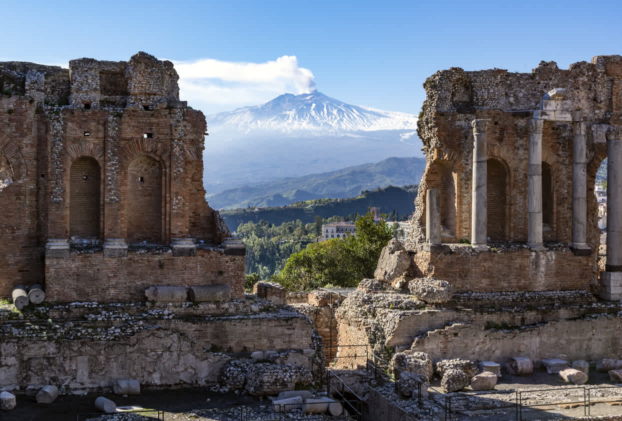 Etna volcano in Sicily seen through the ruins of the ancient amphitheater in Taormina
