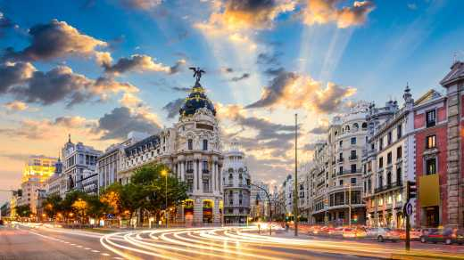 Europe, Spain, Madrid, a busy street corner in Madrid. Traffic streaks by, and the late afternoon sun lights up a blue sky dotted with clouds.