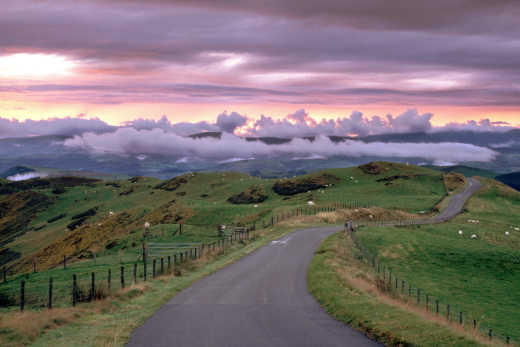 See the hilly area of Powys, pictured here with a storm cloud sunset and winding road, on a Tour of Wales