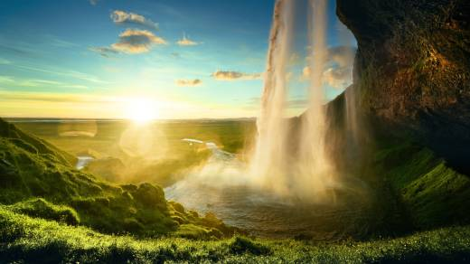 Plan a European Tour package and you'll discover incredible waterfalls, like Seljalandsfoss Waterfall in Iceland, here pictured in the morning mist with the sun rising over green hills.