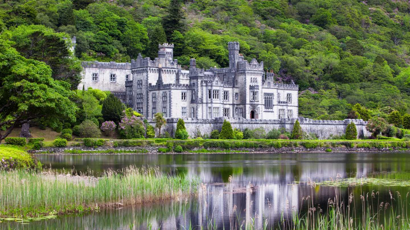 Europe, Ireland, Connemara, Kylemore Abbey surrounded by lush forest and reflected in a grass-lined pond.