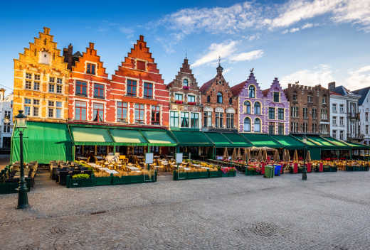 The market in the Grand Place of Antwerp at sunrise, framed by colourful houses typical of Belgian architecture. A city to discover during your holidays in Belgium.