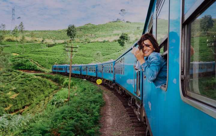 Solo female traveller leaning out window on a train