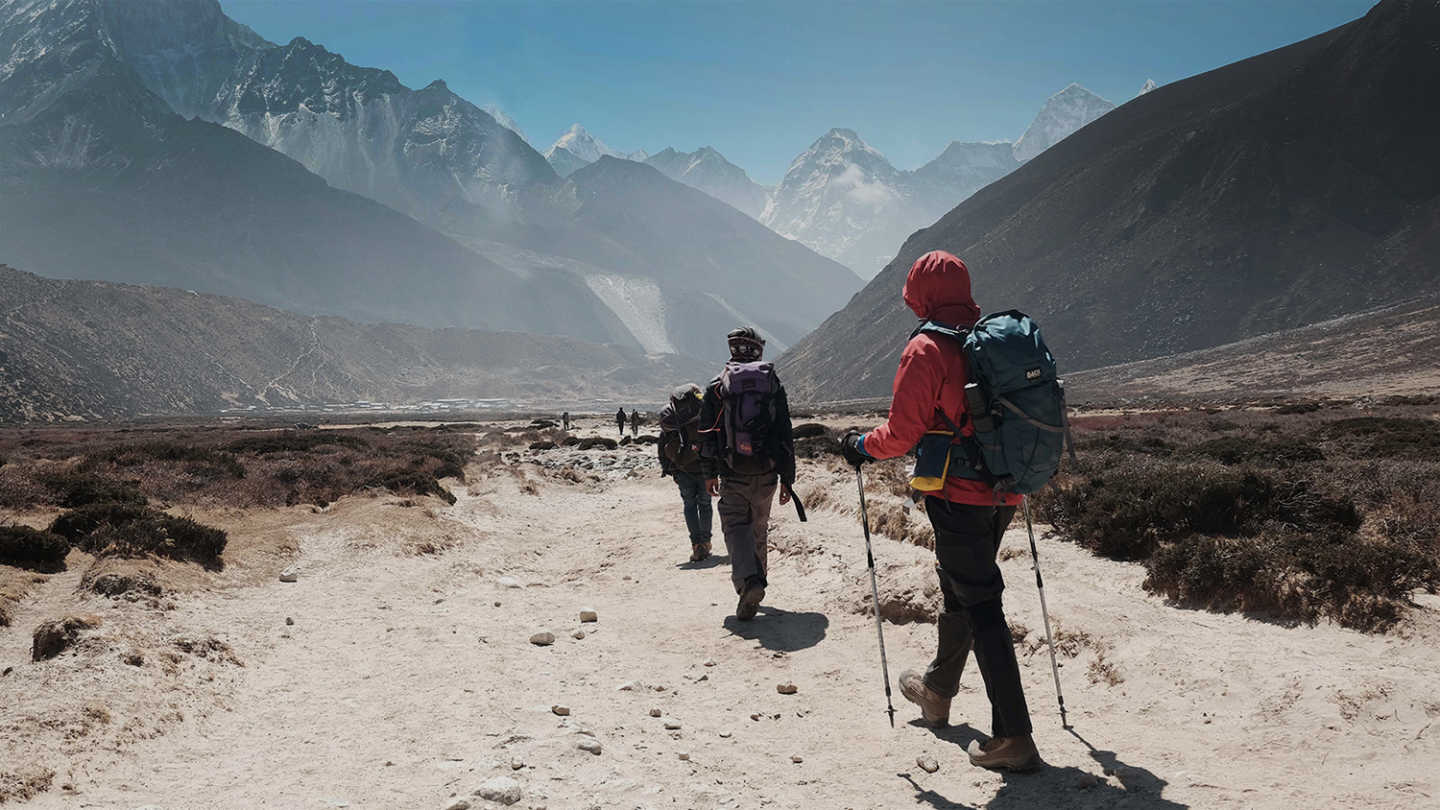 View of hikers hiking in mountainous scenery