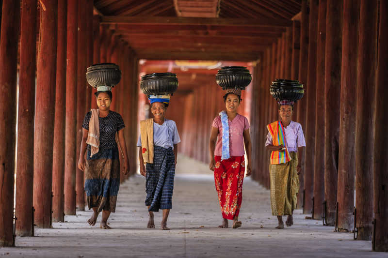 Culture in Myanmar: Burmese women carry rice bowls to the monastery.