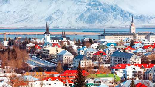 See the Reykjavik skyline, pictured here on a sunny day with mountains in the background, on a Reykjavik vacation.
